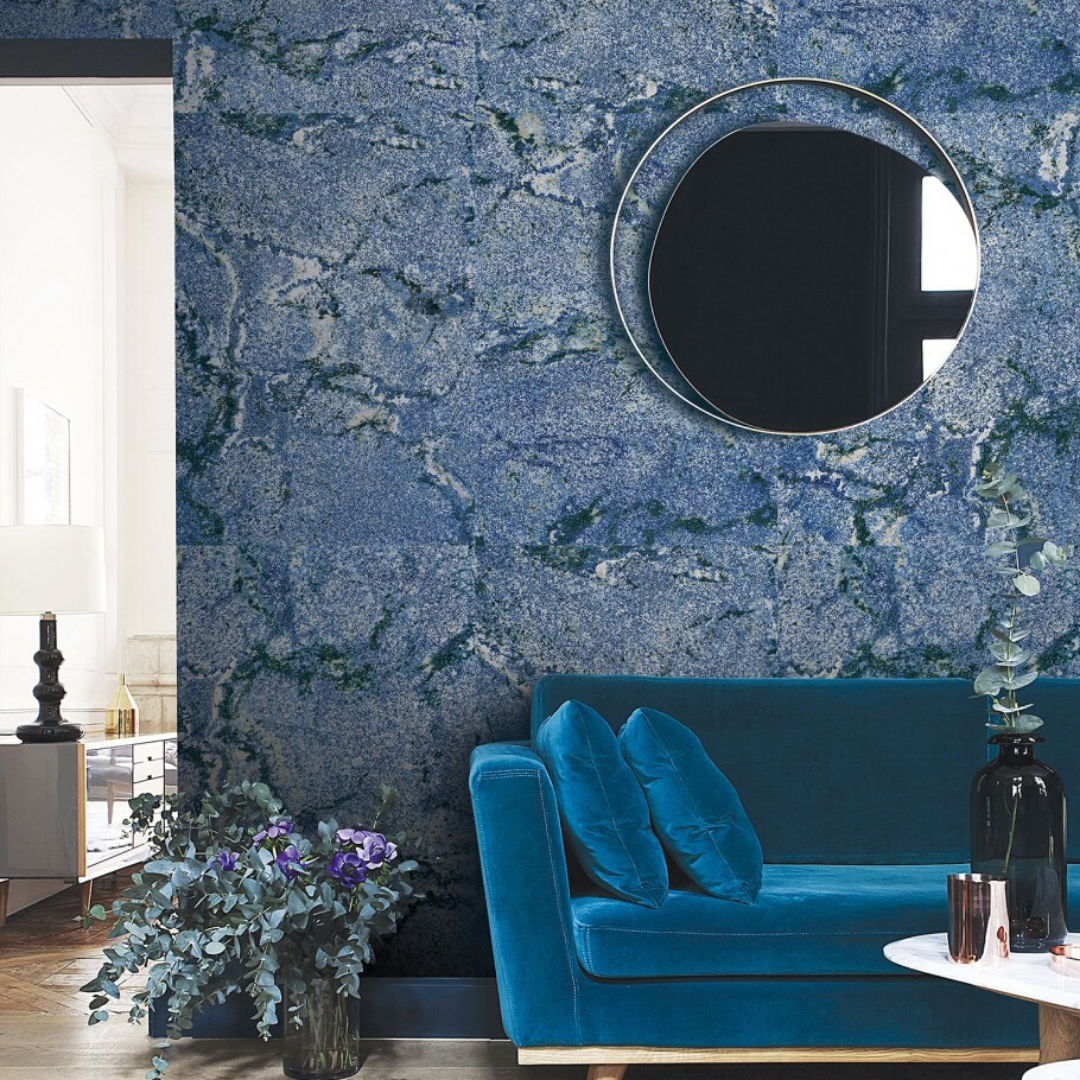 Beautiful stone look porcelain tile in a striking blue with dark veining against a living room wall.