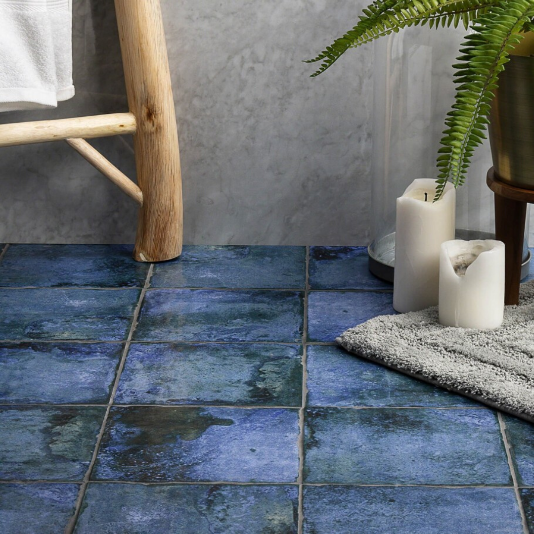 An earthy ombre metallic porcelain floor tile. Plants. Rug.